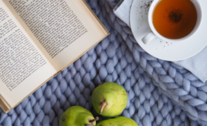 image of cozy blanket, book, fruit and tea