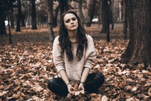 Woman sitting in leaves at park - depression and anxiety