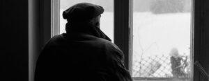 elderly man looking out window
